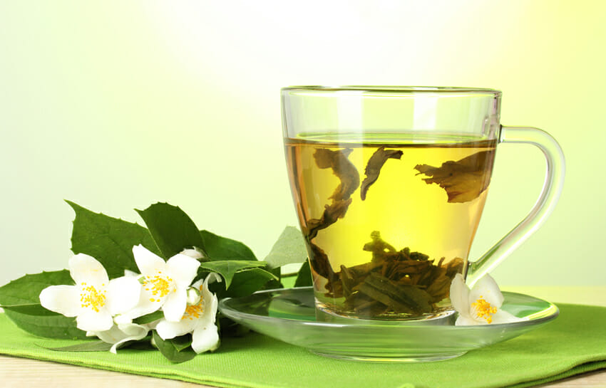 cup of green tea with jasmine flowers against cold