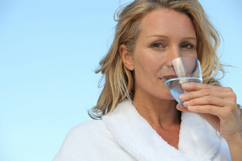 woman drinking water for skin