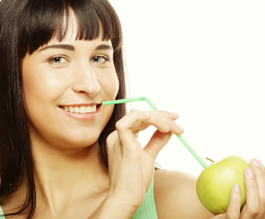 woman with apple and straws
