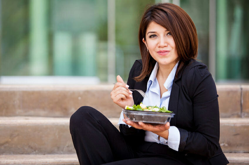business woman eating a healthy salad and relaxing outdoors