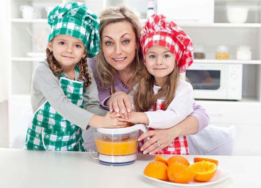 Woman and kids making fresh fruit juice