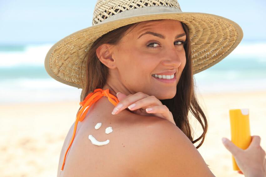 woman applying suncream at the beach - skincare tips
