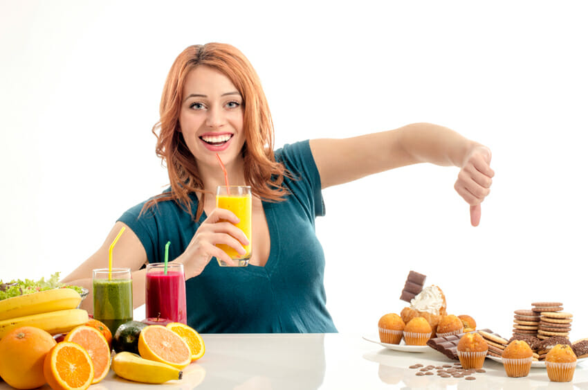 woman choosing between fruits and unhealthy food