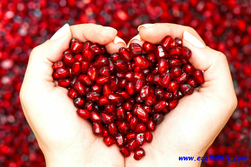 pomegranate seeds shaping heart in hands - sun protective food